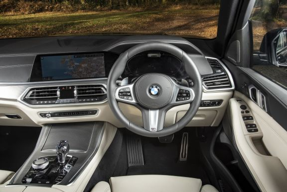 The interior of a BMW X5 with steeringwheel and dashboard in shot