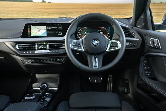 The interior of a BMW 1 Series with steeringwheel and dashboard in shot